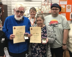 Barry and Ann Appleton proudly show off their Civic Awards with store Manager Mary Banks and fellow