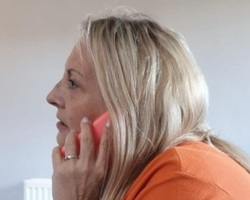 One of our OrangeLine volunteers on the phone (cropped)